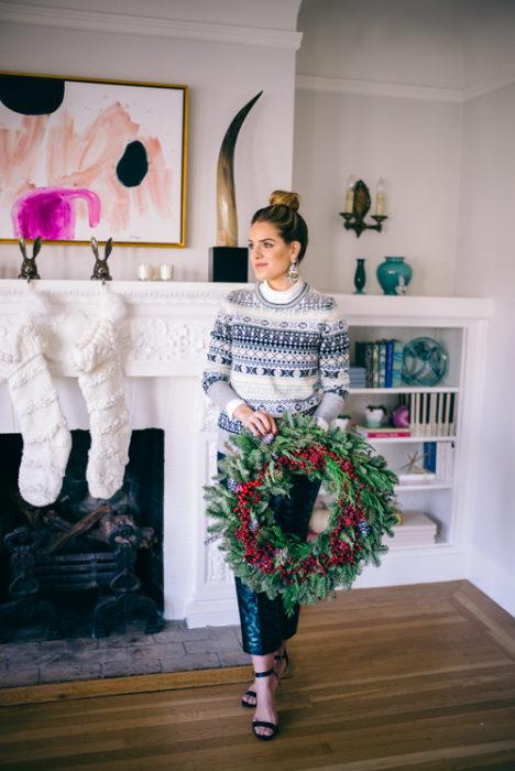 Chica usando un ugly sweter de color gris con blanco y falda de color con brillos