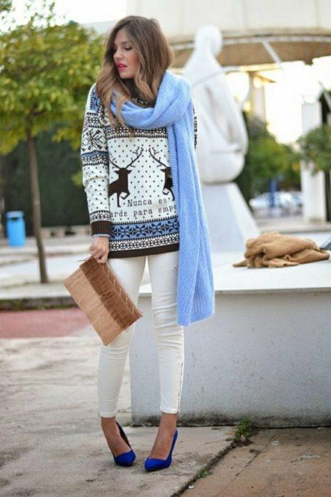 Chica usando un feo suéter navideño con bufanda y pantalón de color blanco