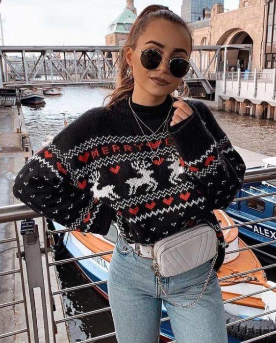 Chica usando un ugly sweter de color negro con jeans y una cangurera