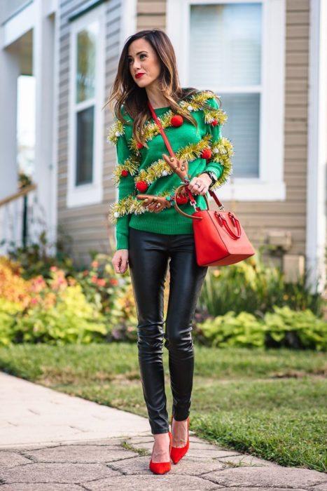 Chica usando un ugly sweter de color verde con unos leggins de color negro