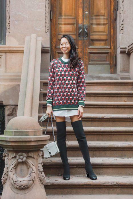 Chica usando un ugly sweter de color verde con rojo y botas color gris