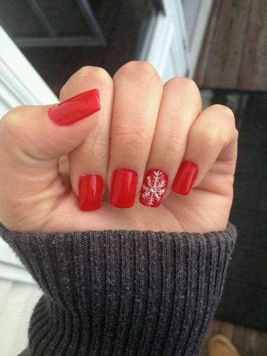 Manicura en rojo con un copo de nieve en blanco