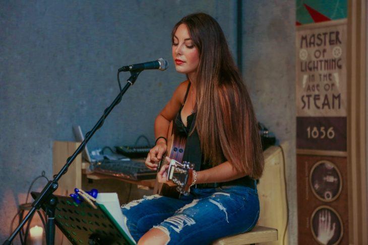 Chica tocando la guitarra y cantando acapela