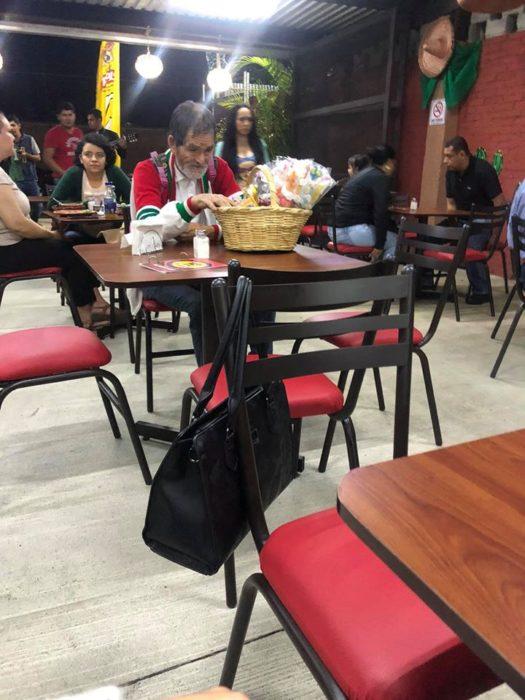 Señor que vende paletas de bombón sentado en un restaurante