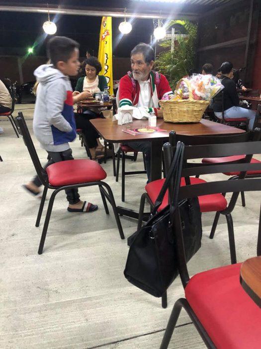 Niño invitando a un señor indigente que vende dulces a cenar