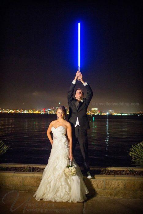 Novio sosteniendo un sable de luz mientras posa junto a su esposa en una sesión de fotos