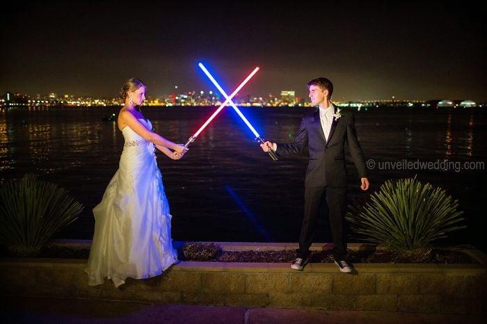 Novios sosteniendo sables de luz mientras posan para la sesión de fotos de su boda