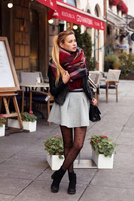Chica usando una falda gris, chaqueta, bufanda y medias mientras posa para una foto