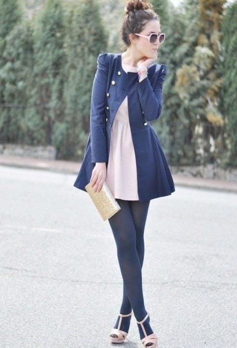 Chica usando un vestido de color rosa, abrigo azul, medias y sandalias rosas