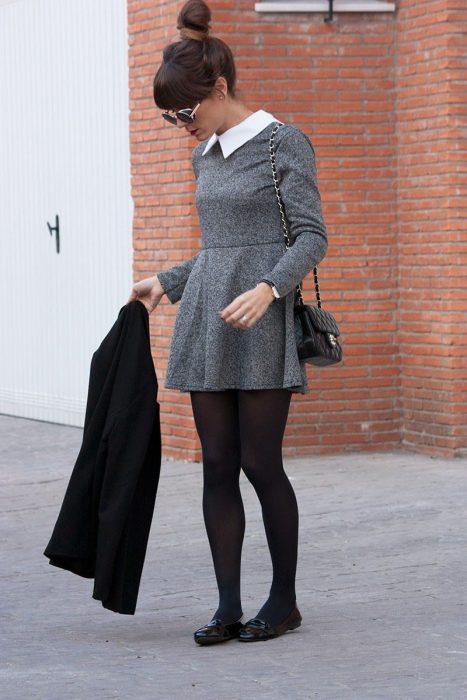 Chica usando un vestido de color gris con medias y zapatos bajos