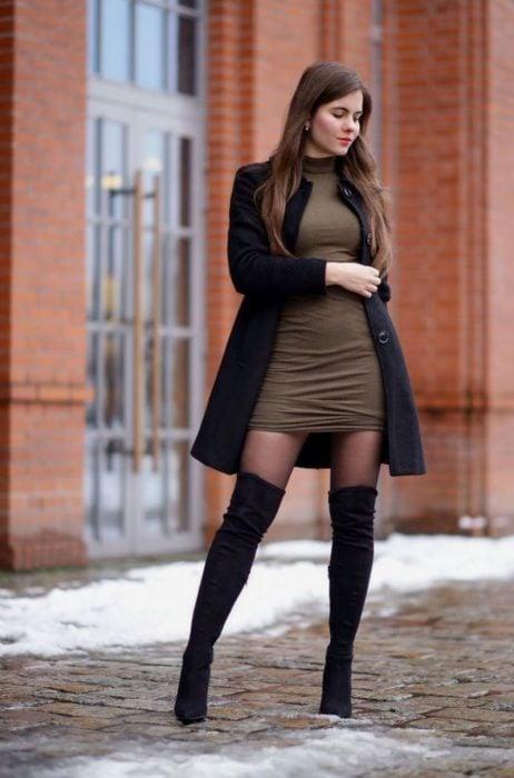 Chica usando un vestido de color café con abrigo, medias y botas negras