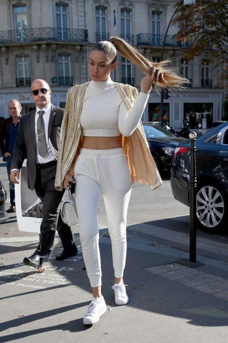 Gigi hadid caminando hacia su departamento mientras usa un conjunto de pants en color blanco