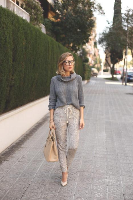 Chica usando pants de color beige con un abrigo de color gris y zapatos de tacón