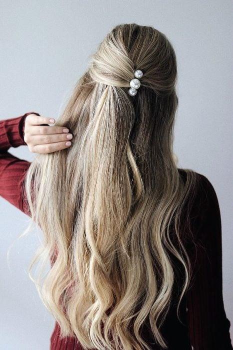 Chica mostrando su peinado de media coleta con broches de perla