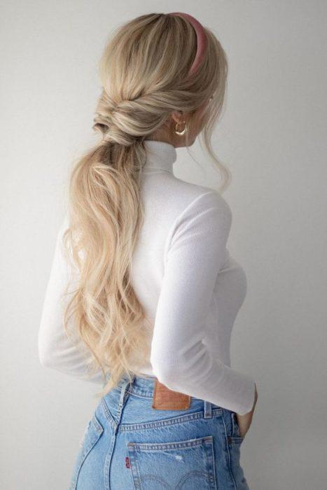 Chica mostrando su cabello con coleta baja y ondulada