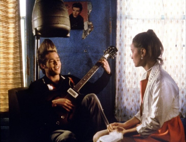 Brad Pitt con un peinado alto y sentado mientras toca la guitarra