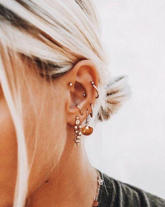 Chica con cabello rubio claro y ´pendientes pequeños en el oído