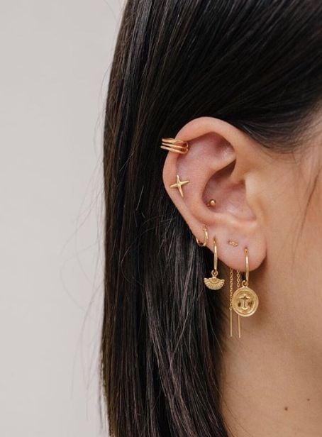 Chica mostrando sus pendientes dorado en el oído