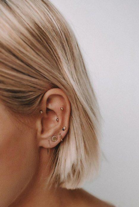 Chica mostrando sus multiples pendientes en el oído izquierdo
