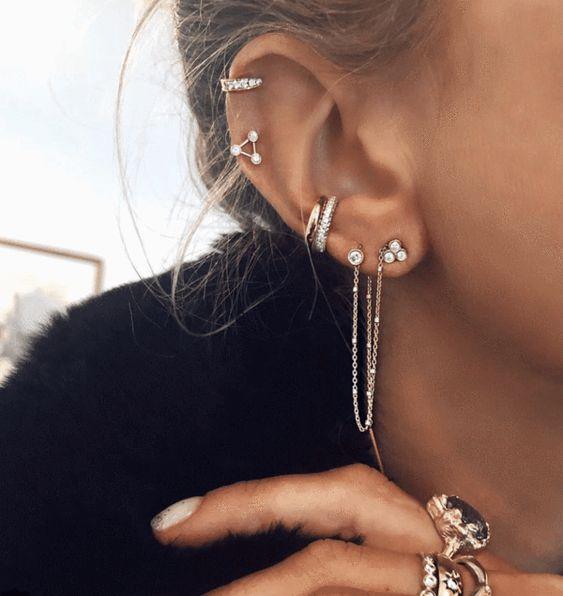 Chica con pendientes plateados en todo el oído