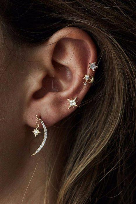 Chica mostrando sus pendientes pequeños en el oído izquierdo de estrella y luna