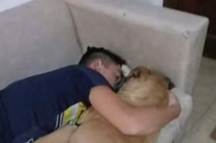 Chico abrazando a su perrita sobre un sofá