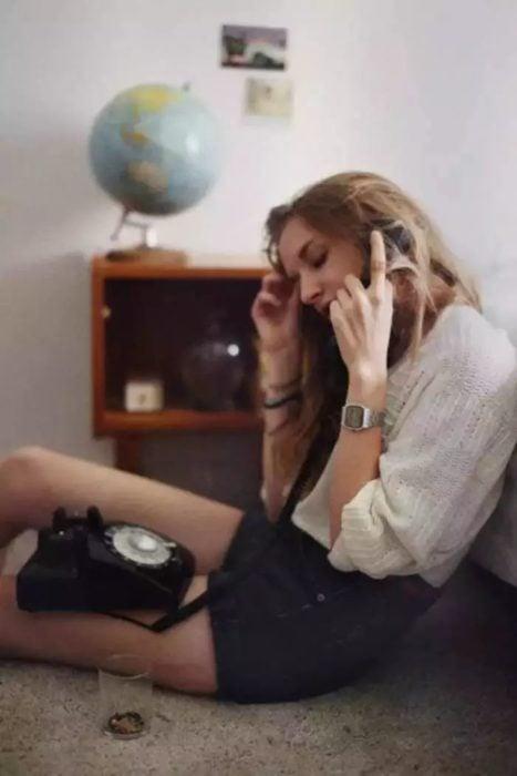 Chica e su habitación llamando por teléfono