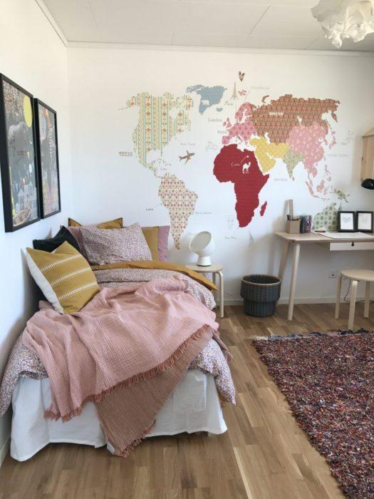 Habitación de chica decorada con mapas y cuadros