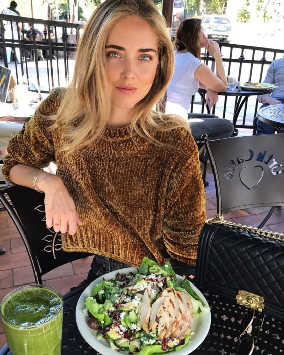 Chica en un restaurante comiendo ensalada de pollo