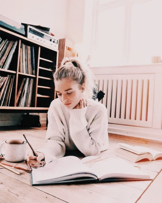 Chica estudiando dentro de su recamara