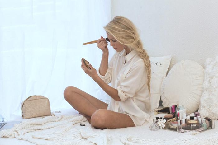 Chica maquillándose en su cama