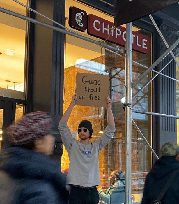 Chico con una pancarta protestando por que el guacamole debería ser gratis