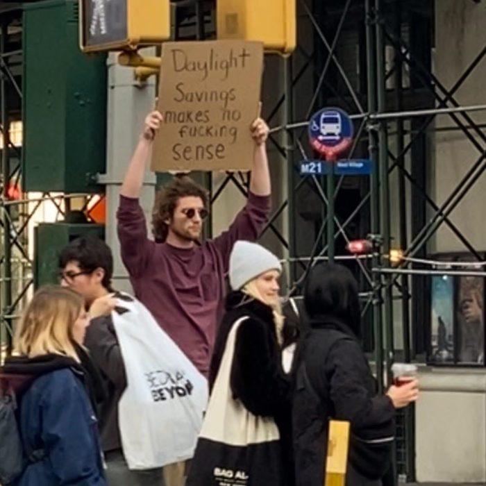 Chico con una pancarta protestando por el horario de verano en las calles de Nueva York