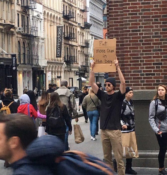 Chico con una pancarta protestando por el aire en las papitas fritas