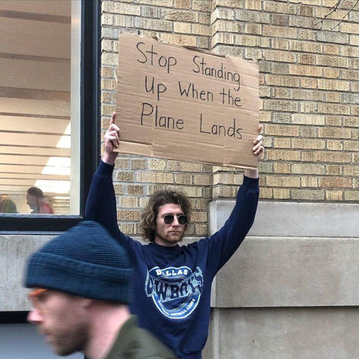 Chico con una pancarta protestando por la gente que se para en los aviones