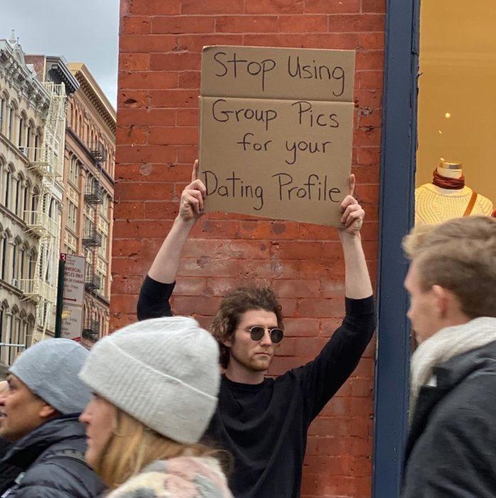 Chico protestando con una pancarta sobre las citas en línea