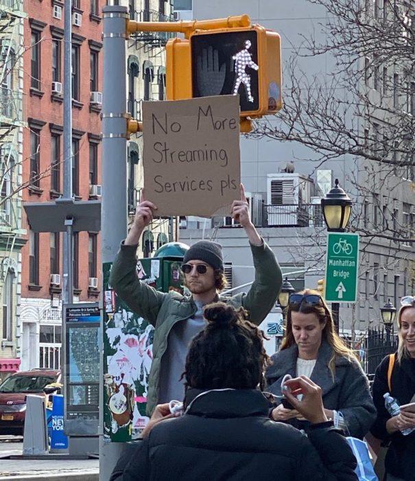 Chico levantando un cartel con una protesta en contra del servicio de streamign