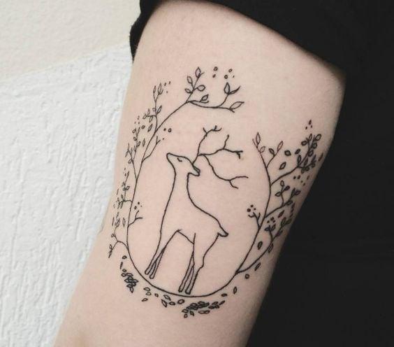 Tatuaje de renos rodeado de muerdago navideño