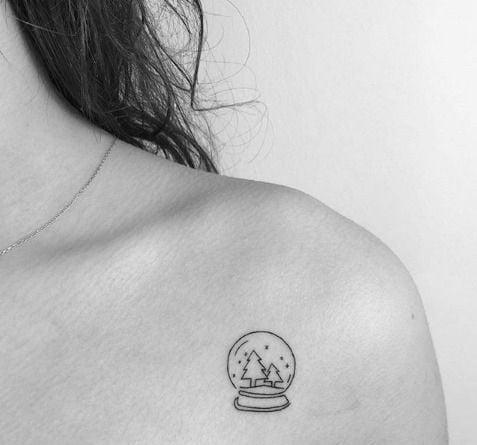Chica mostrando su tatuaje de bola de nieve de cristal