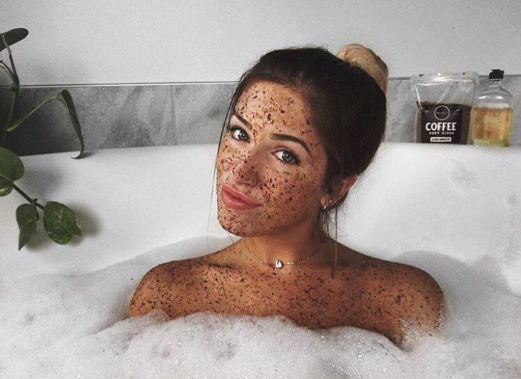 Chica dentro de la ducha con mascarilla de café