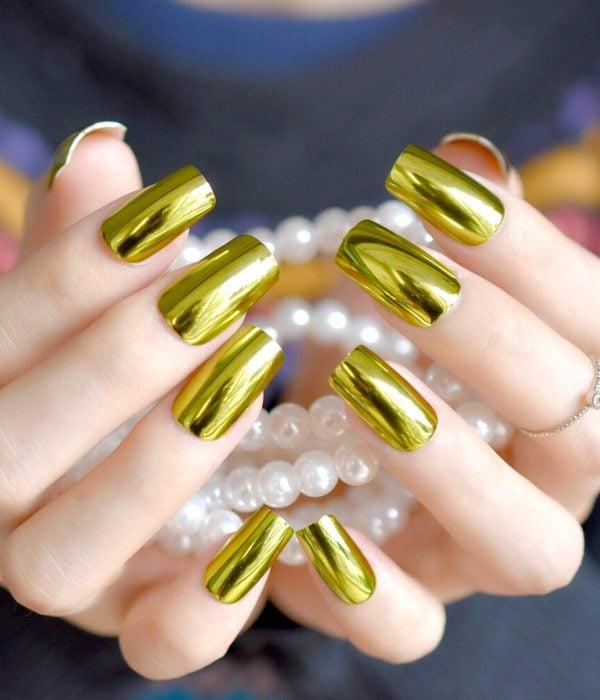 Manicure dorado para la fiesta de Año Nuevo; manos de uñas largas y cuadradas sosteniendo perlas