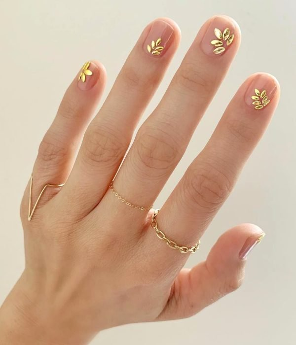 Manicure de hojas doradas para la fiesta de Año Nuevo; uñas cortas