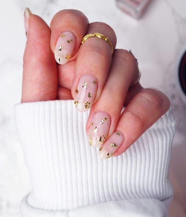 Manicure con detalles dorados para la fiesta de Año Nuevo; uñas largas en forma de almendra