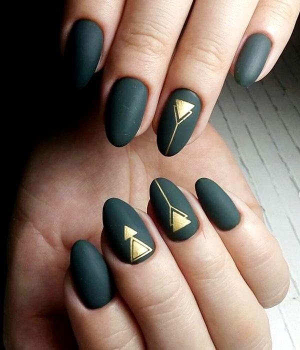 Manicure verde con triángulos dorados para la fiesta de Año Nuevo; uñas en forma de almendra
