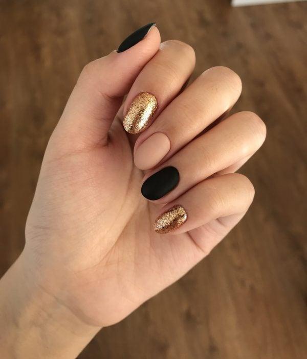Manicure esmalte negro, rosa y dorado con brillos para la fiesta de Año Nuevo; uñas en forma de almendra