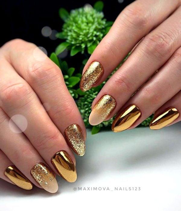 Manicure dorado para la fiesta de Año Nuevo; manos con uñas largas en forma de almendra