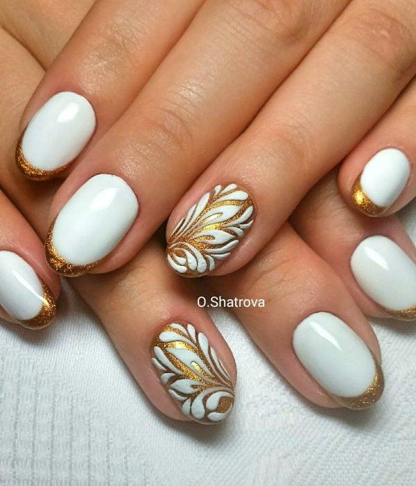 Manicure blanco con dorado para la fiesta de Año Nuevo; uñas cortas en forma de almendra