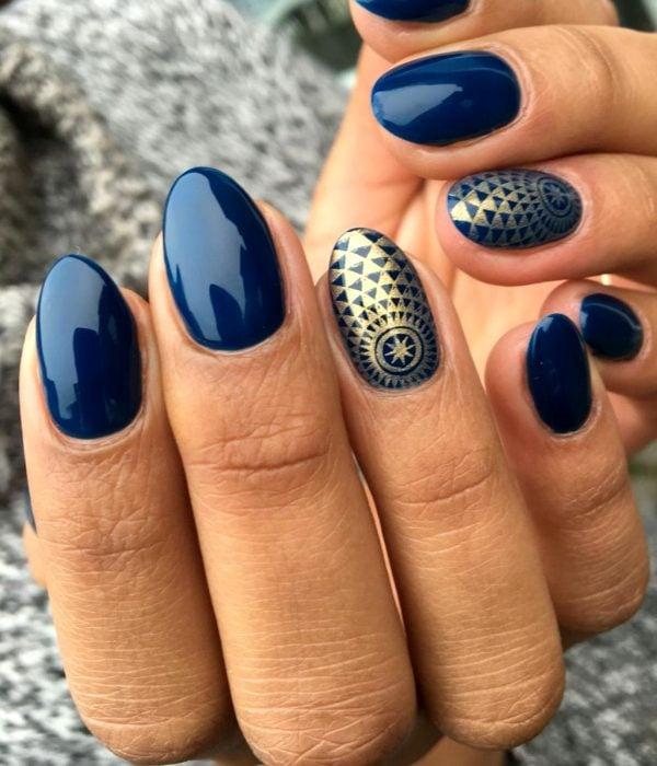Manicure azul con figuras doradas para la fiesta de Año Nuevo; uñas largas en forma de almendra