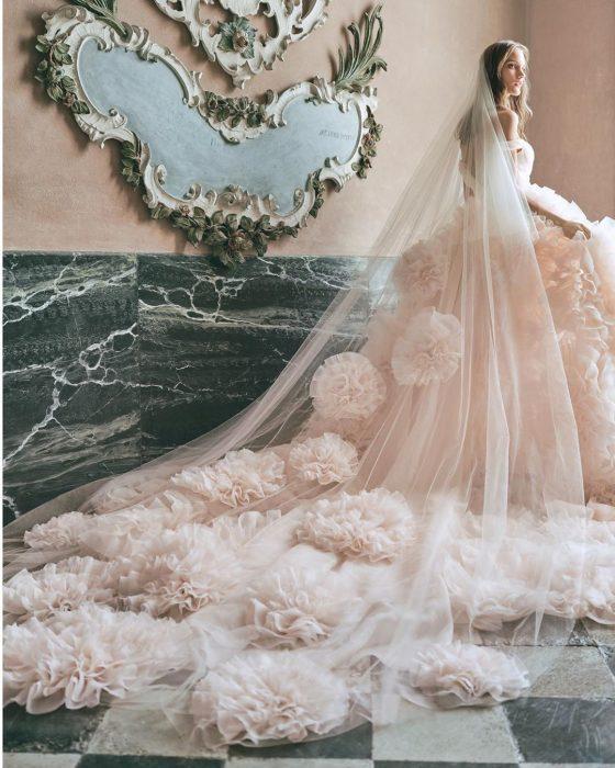 Chica con un vestido de novia en color blanco con estampado floral y un velo largo con pompones