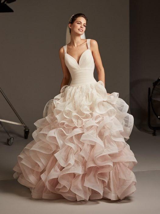 Chica con un vestido de novia en colores degradados con en rosa con varias capas de tul